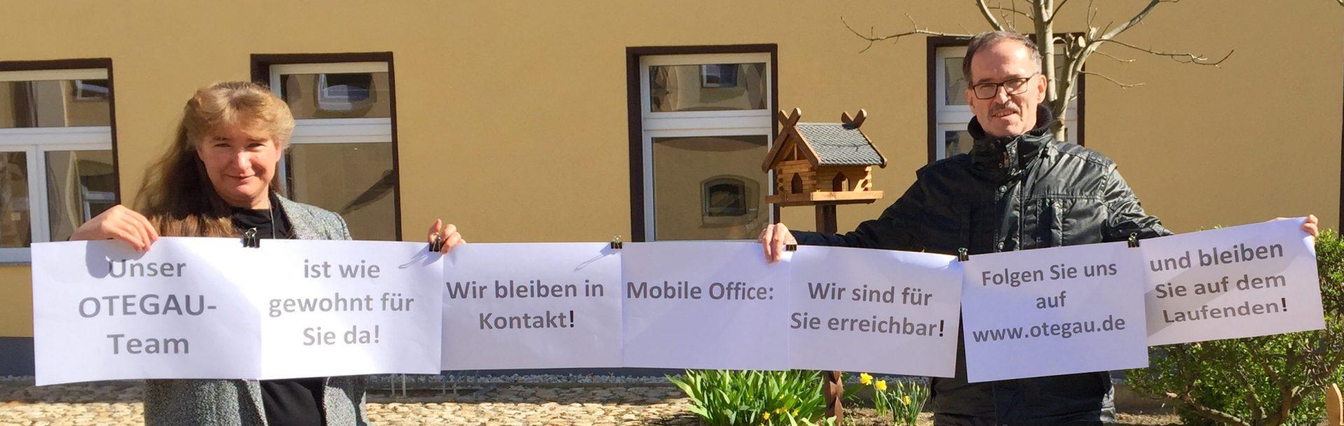 """Das Bild zeigt die Geschäftsführerin Suzanne Vöcking mit Prokurist Michael Breul mit einem Spruchbanner auf welchem steht: """"Unser OTEGAU Team ist wie gewohnt für Sie da! Wr bleiben in Kontakt! Mobile Office: Wir sind für Sie erreichbar! Folgen Sie uns auf www.otegau.de und bleiben auf dem Laufenden!"""